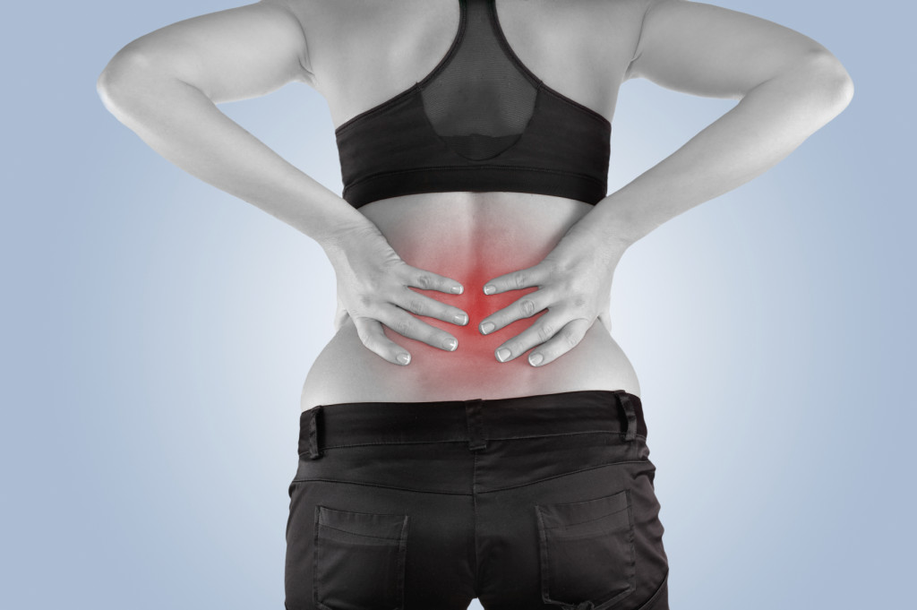 Back pain. Athletic woman in black sportswear standing and rubbing the muscles of her lower back, cropped torso portrait.